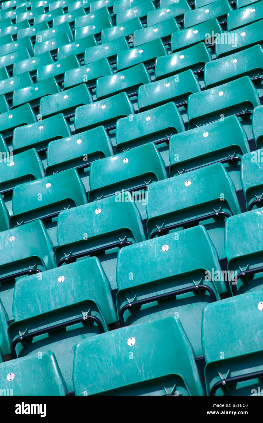 Rows of empty green plastic seats in a sports stadium - Stock Image