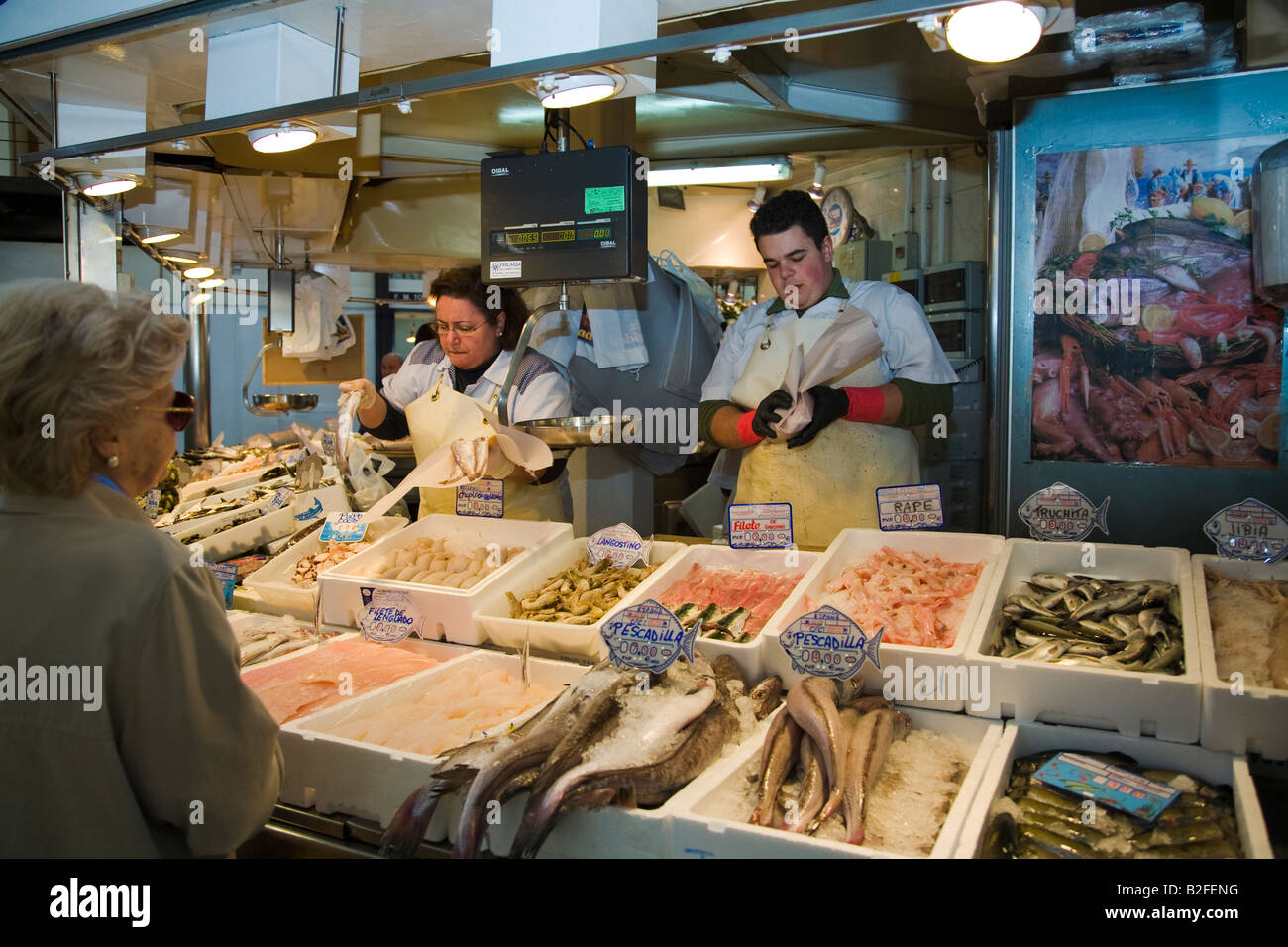 SPAIN Salamanca Man and woman prepare fish and seafood for customers at indoor market seafood and fish displayed - Stock Image