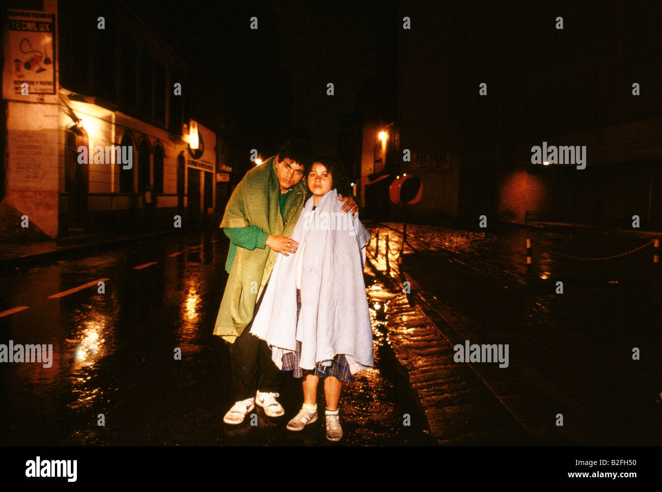 a teenage couple beg on the street at night - Stock Image