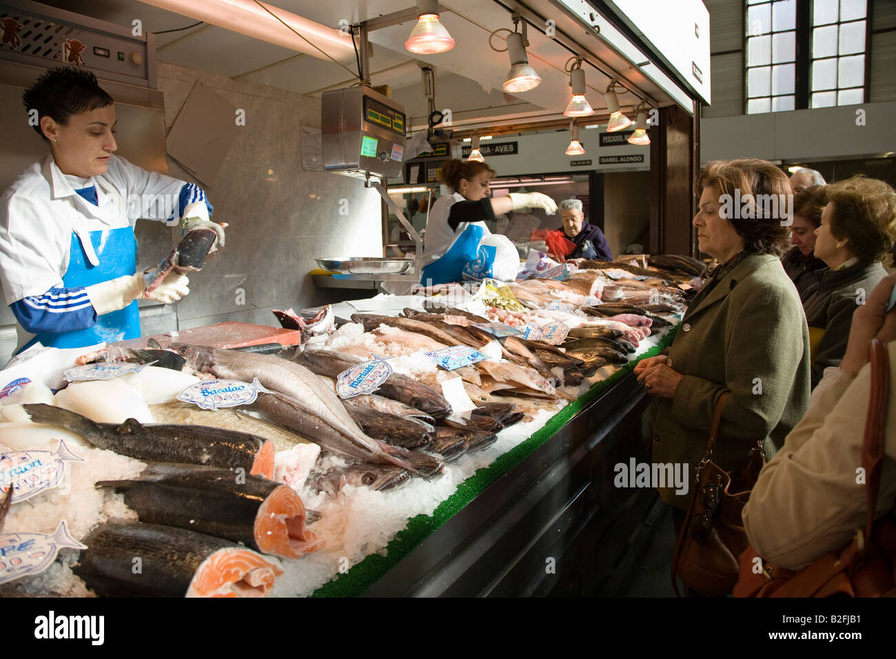 SPAIN Salamanca Women and men shop at fish monger at indoor market vendor show fresh fish to customer - Stock Image