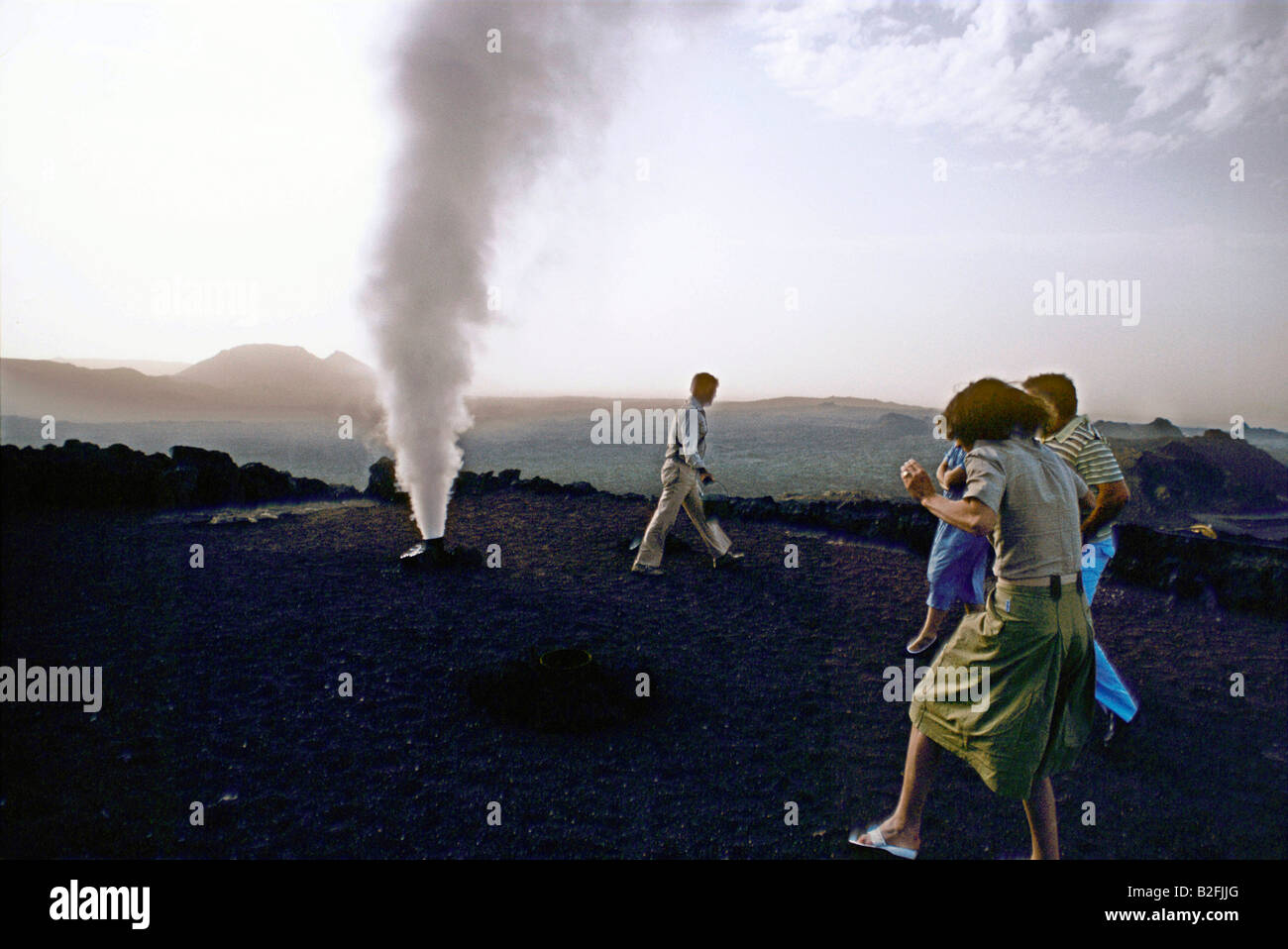 tourists watch a volcanic steam fumerole at timanfaya fire mountain Stock Photo