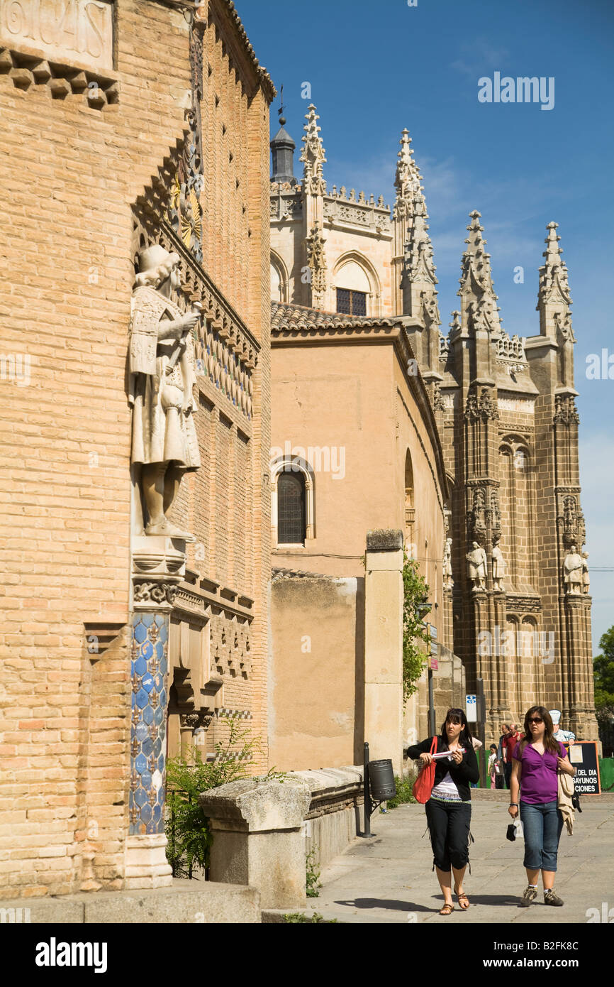 SPAIN Toledo Two women walk down street San Juan de los Reyes Monasterio spires in background - Stock Image