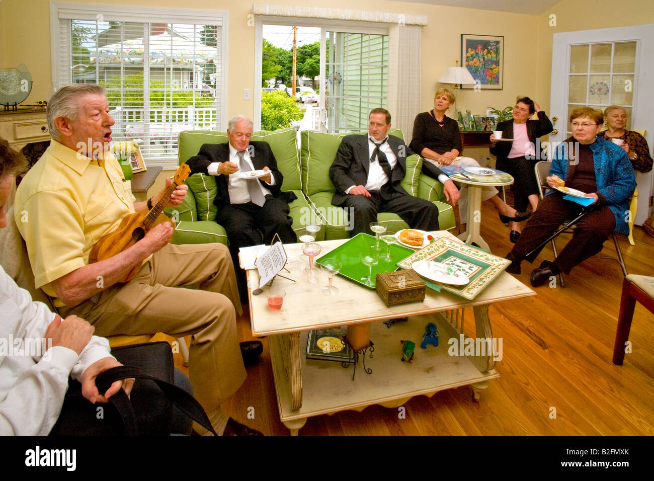 An elderly musician plays Irish folks songs on a ukelele for an appreciative audience in Stoneham Massachusetts - Stock Image