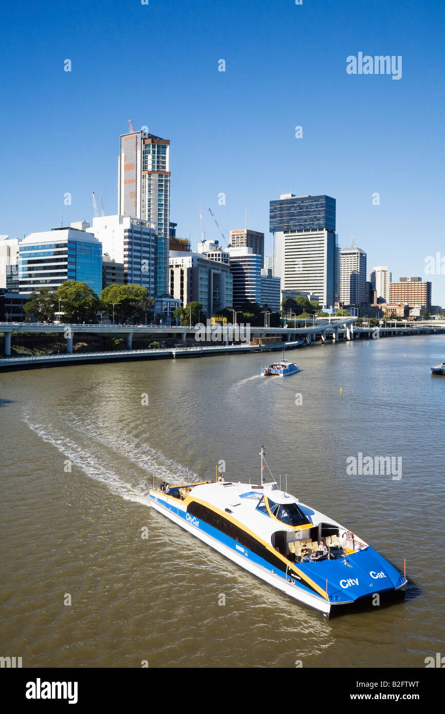 A CityCat ferry cruises along the Brisbane River with city skyline beyond.  Brisbane, Queensland, AUSTRALIA - Stock Image
