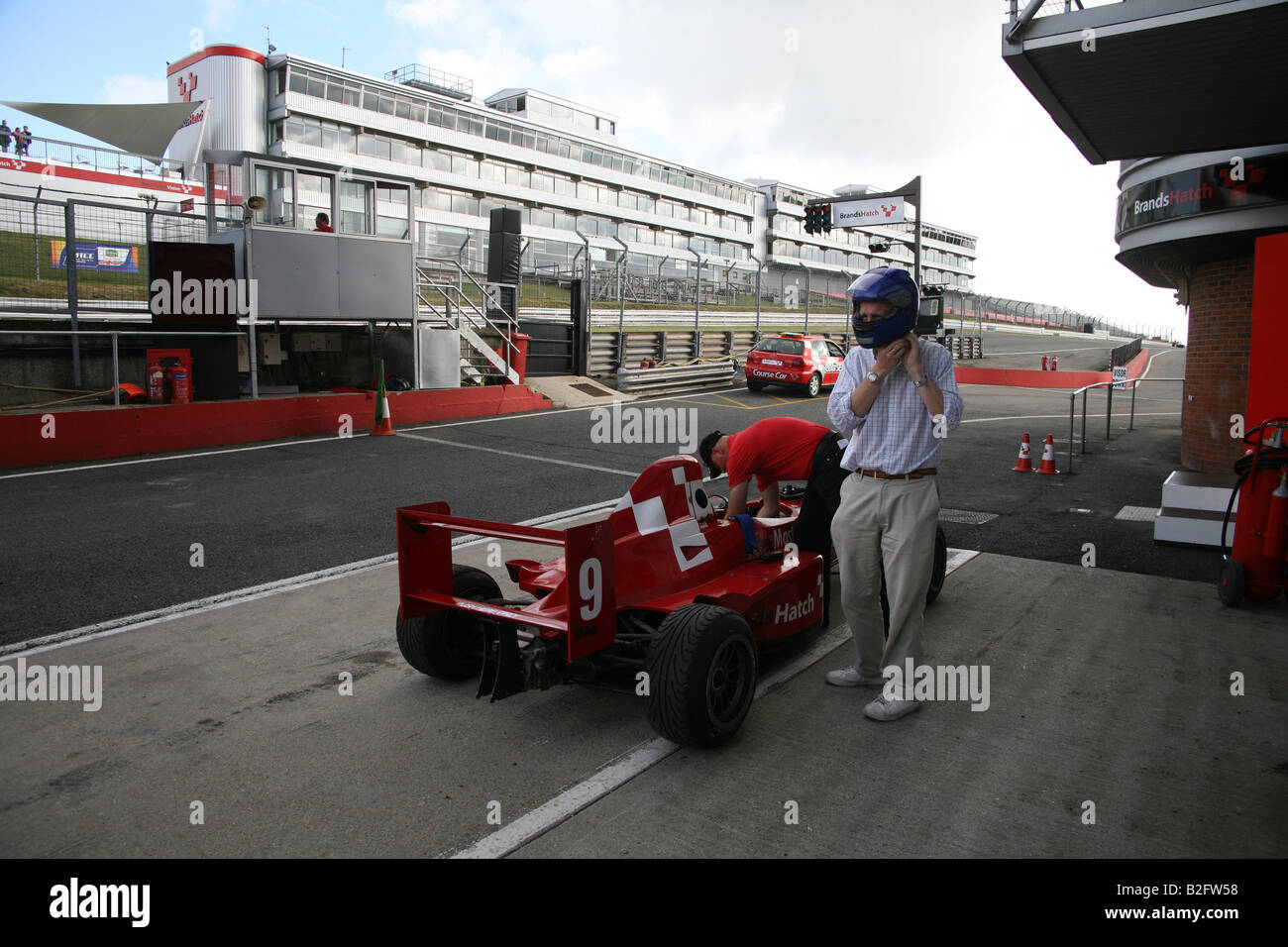 Man walking from a racing car after a drive at Brands Hatch - Stock Image