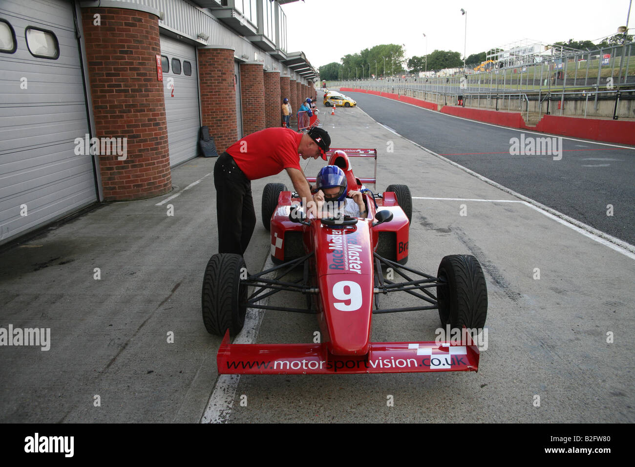Man sitting in a racing car at Brands Hatch - Stock Image