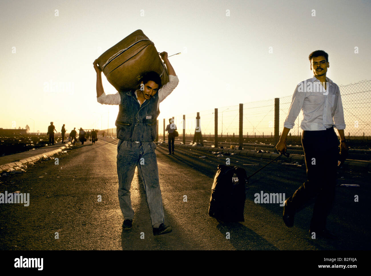 two refugee men carry possessions down a road, during gulf crisis - Stock Image