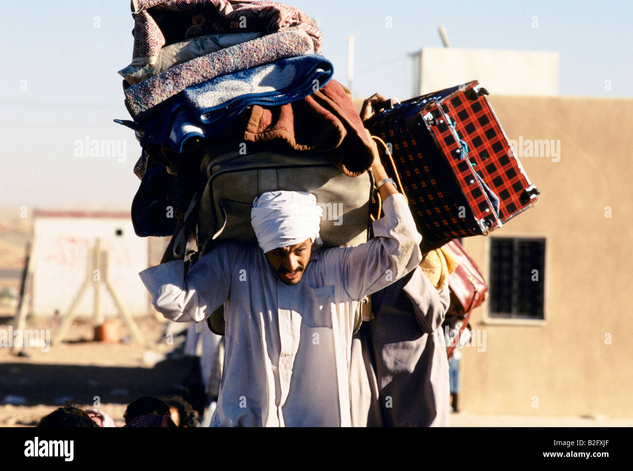 refugee man carrying all his luggage, during gulf crisis - Stock Image
