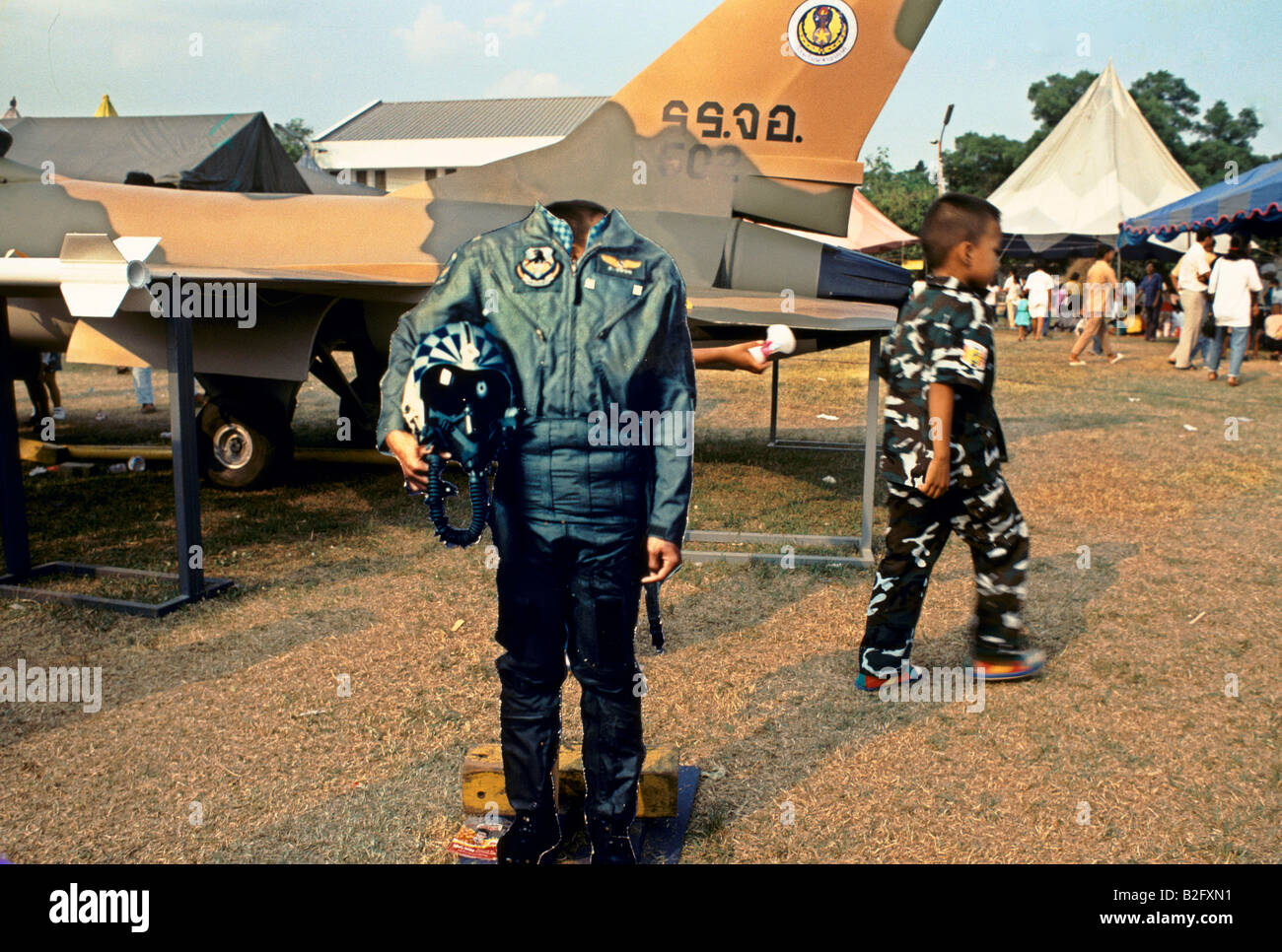 Young boy in camouflage fighter pilot overalls, model of airforce uniform and model jet plane - Stock Image