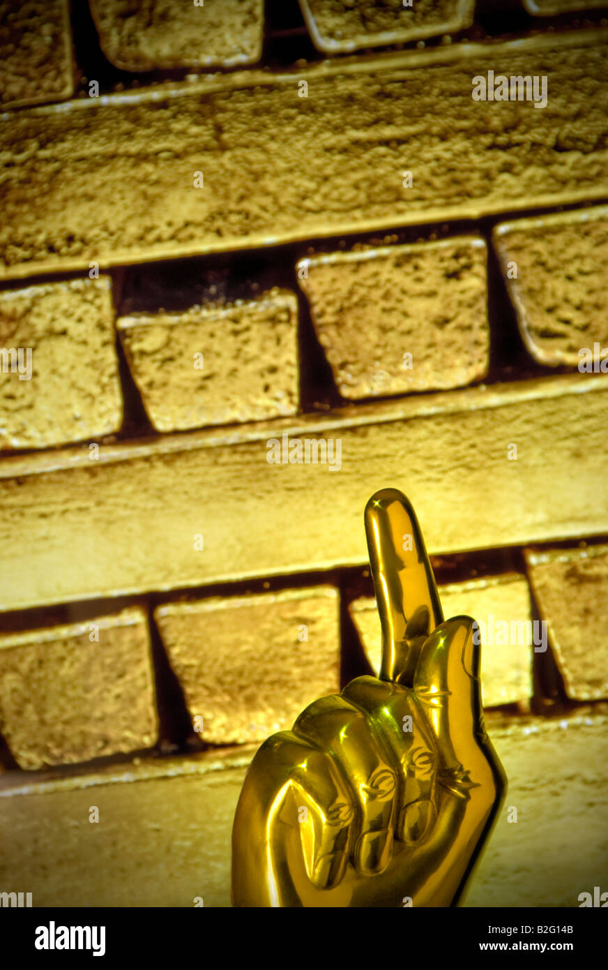 Concept image of increasing global price of gold with 'Gold Finger' pointing up with solid gold bullion - Stock Image