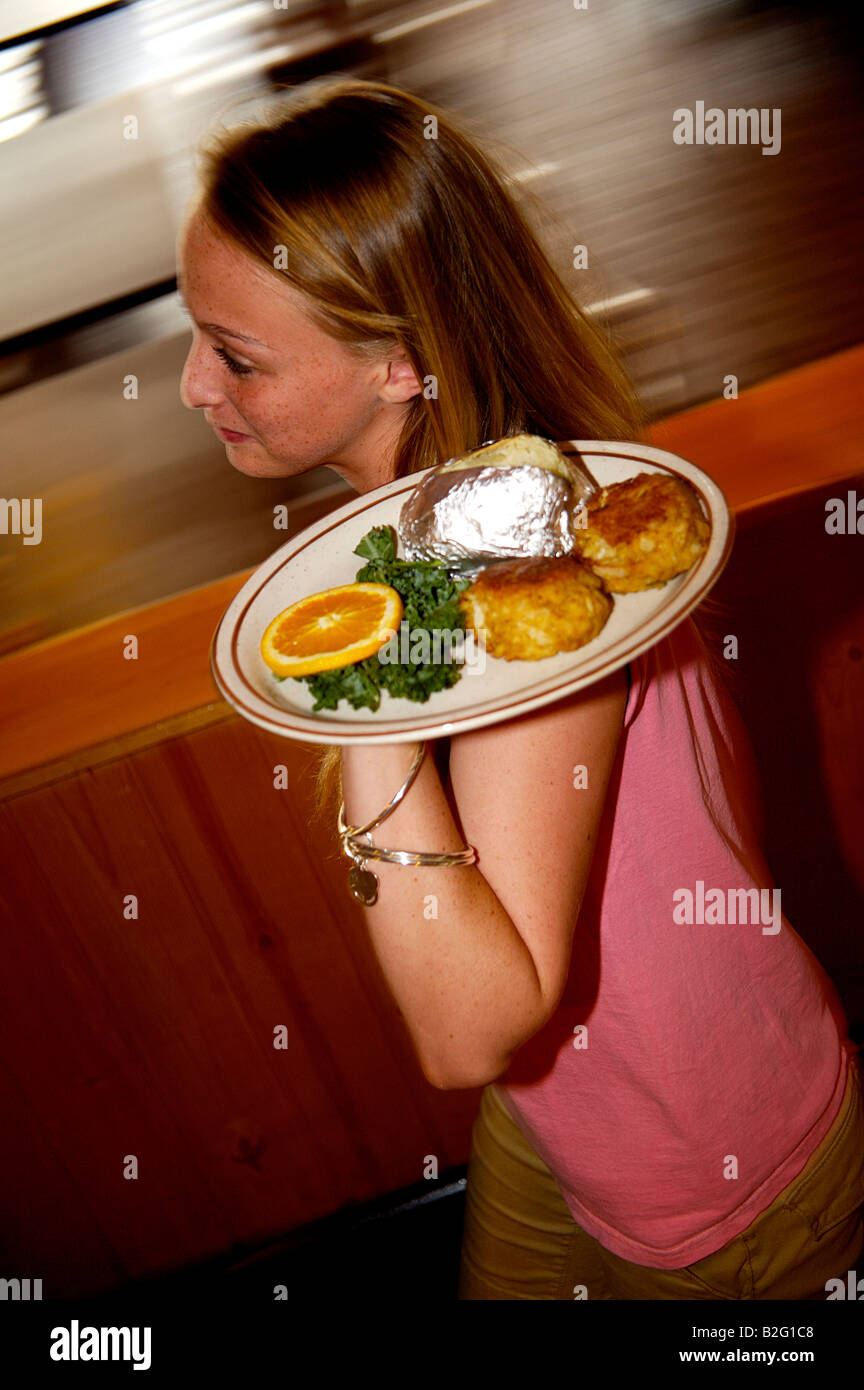 Waitress Carrying Crabcake Dish In Restaurant At Mikes Crabhouse In