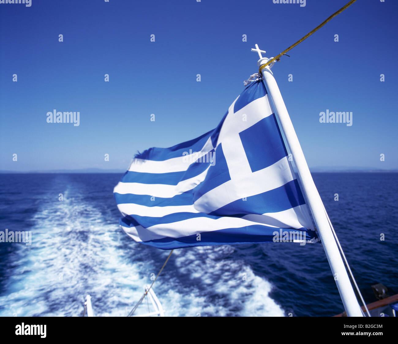 Griechenland-Flagge auf einem Ausflugsschiff, Blick ueber das Schiffsheck, schaeumendes Meer, Aegaeisches Meer - Stock Image