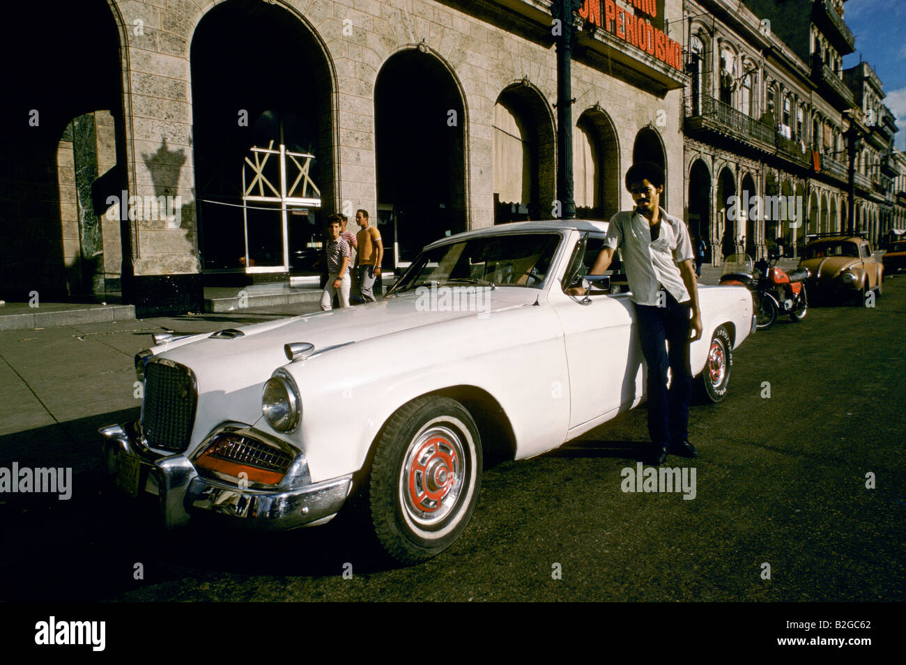 Man standing next to his white classic American car, parked in a street in Havana, Cuba - Stock Image