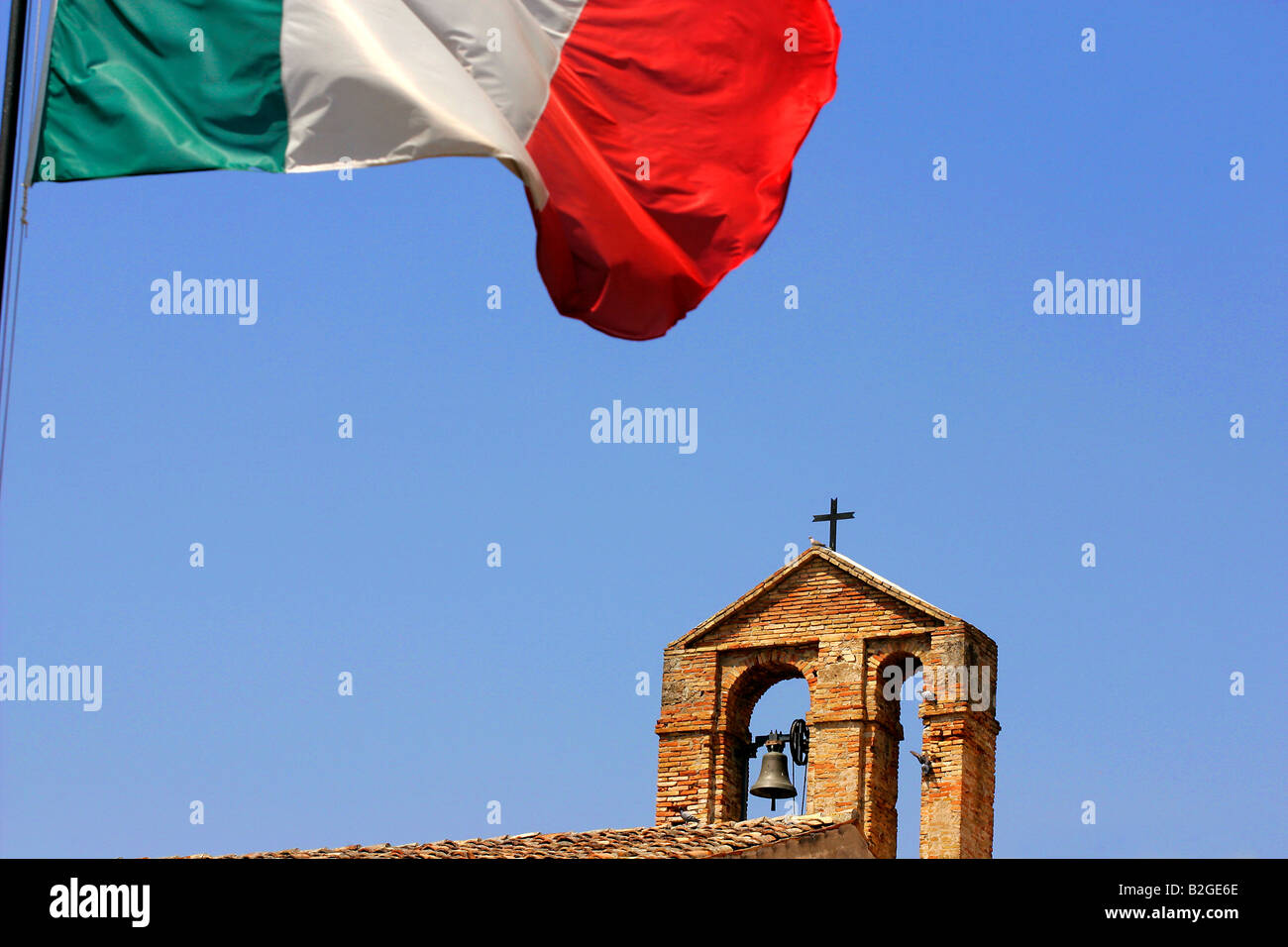 A church belltower and Italian tricolore flag. - Stock Image