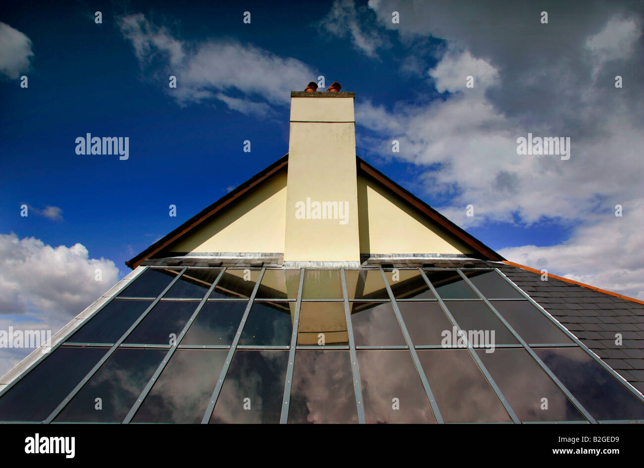 Solar panels on a rooftop in Devon UK reflecting a pitched roof and chimney against a blue sky with clouds. - Stock Image