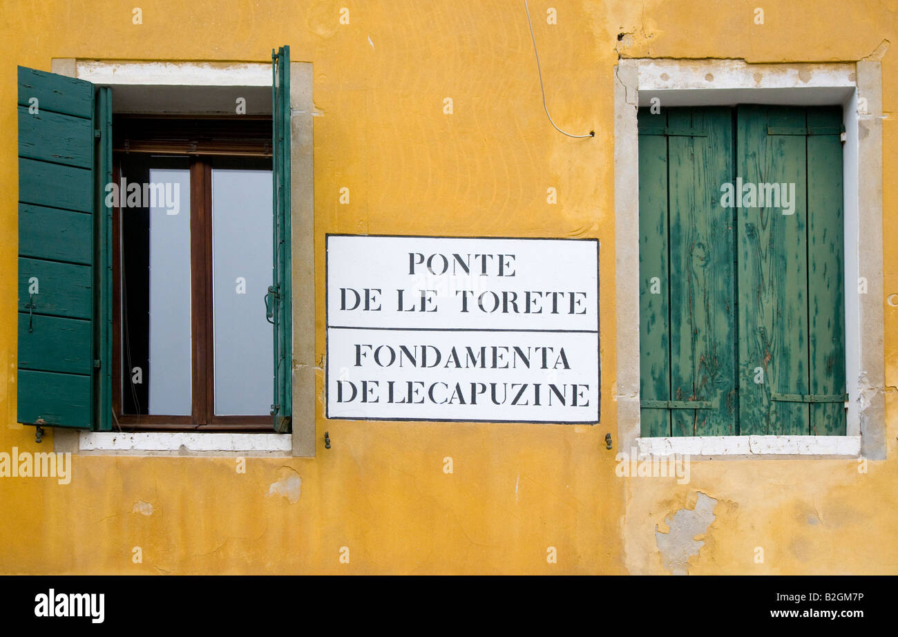 Ponte del le Torete sign on yellow ochre building with green shutters Venice Italy - Stock Image