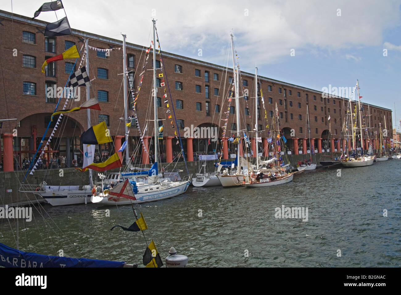 Liverpool Merseyside England UK July View across the redeveloped Albert Dock with some of the tall sailing ships Stock Photo