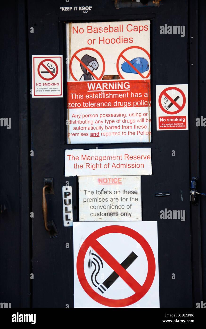 Warning sign on pub door anti hoodies  drugs  baseball caps. - Stock Image