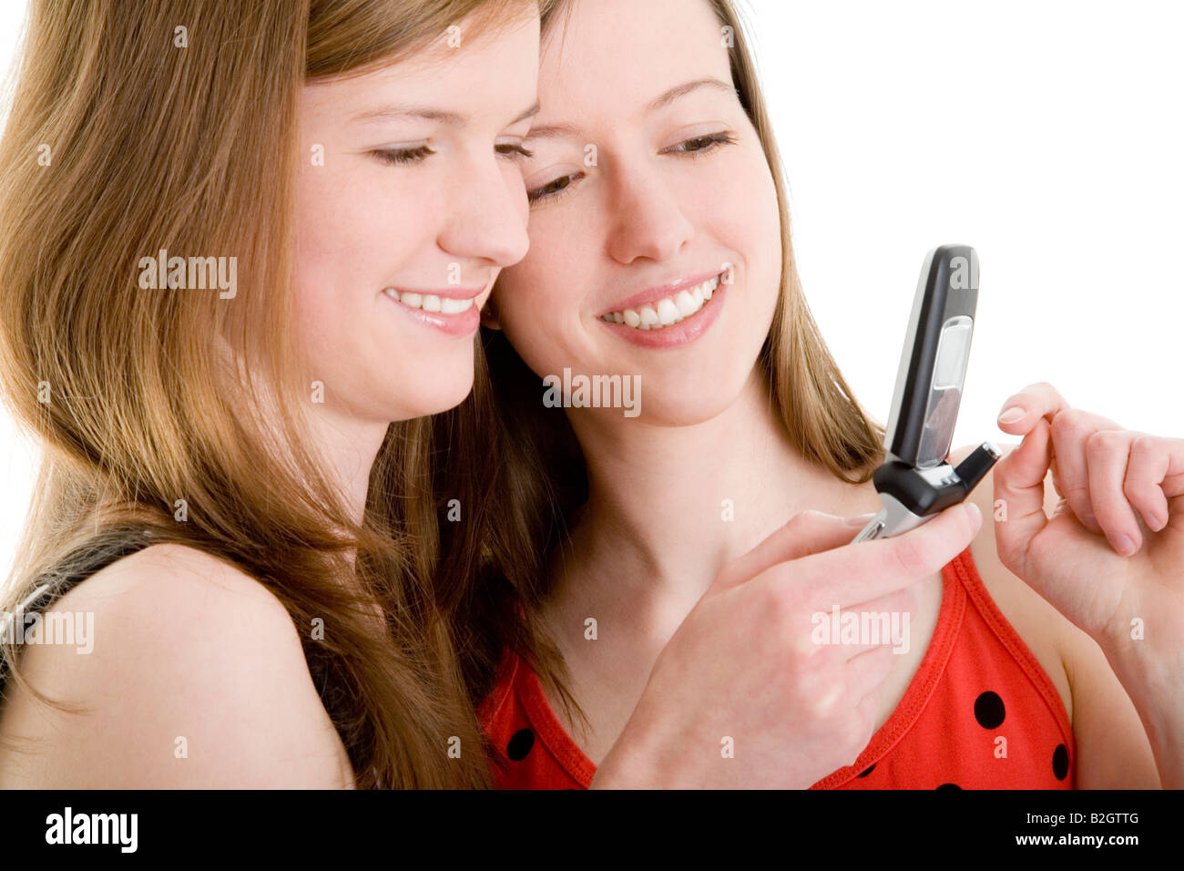 writing message sms mobile female friends teenagers fun happy smiling girls women young smiling people girl friends - Stock Image