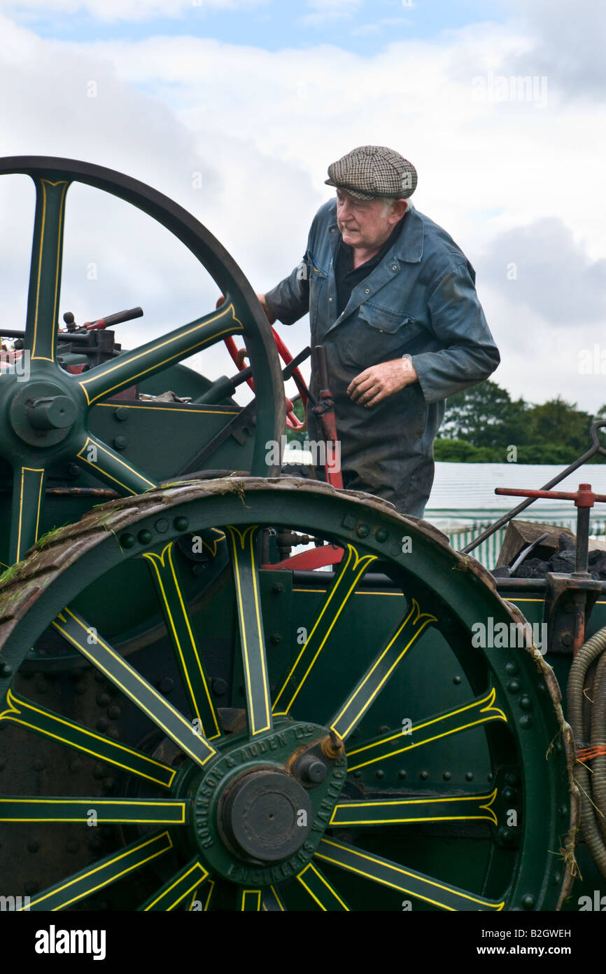 Man driving a Robinson and Auden Traction Engine at Masham Steam Rally - Stock Image