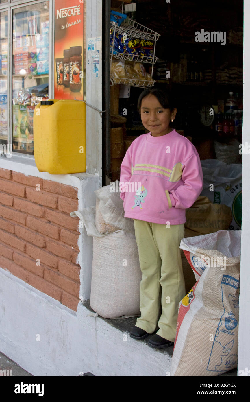 Young girl standing in shop doorway, pink jumper, facing.70353_Ecuador_Otavalo - Stock Image