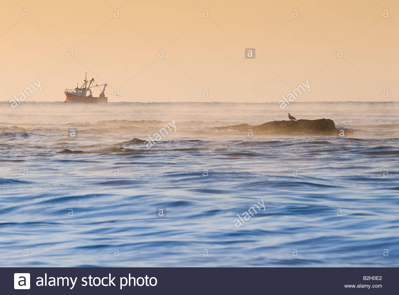 Fishing boat at dawn, off the coast of East Devon. - Stock Image