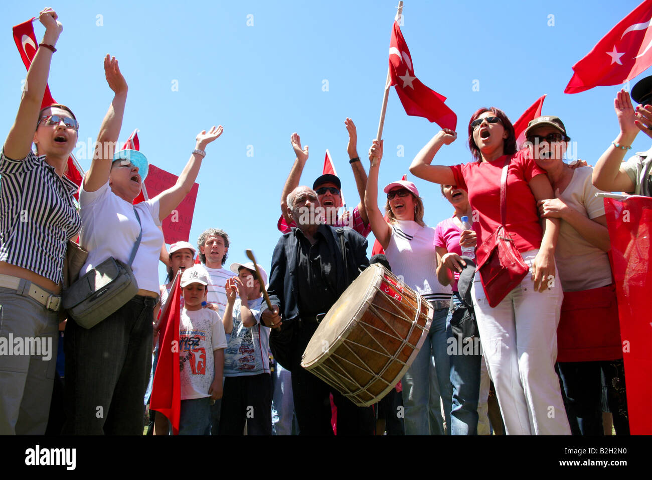 people are marching singin and dancing with turkish flags in the