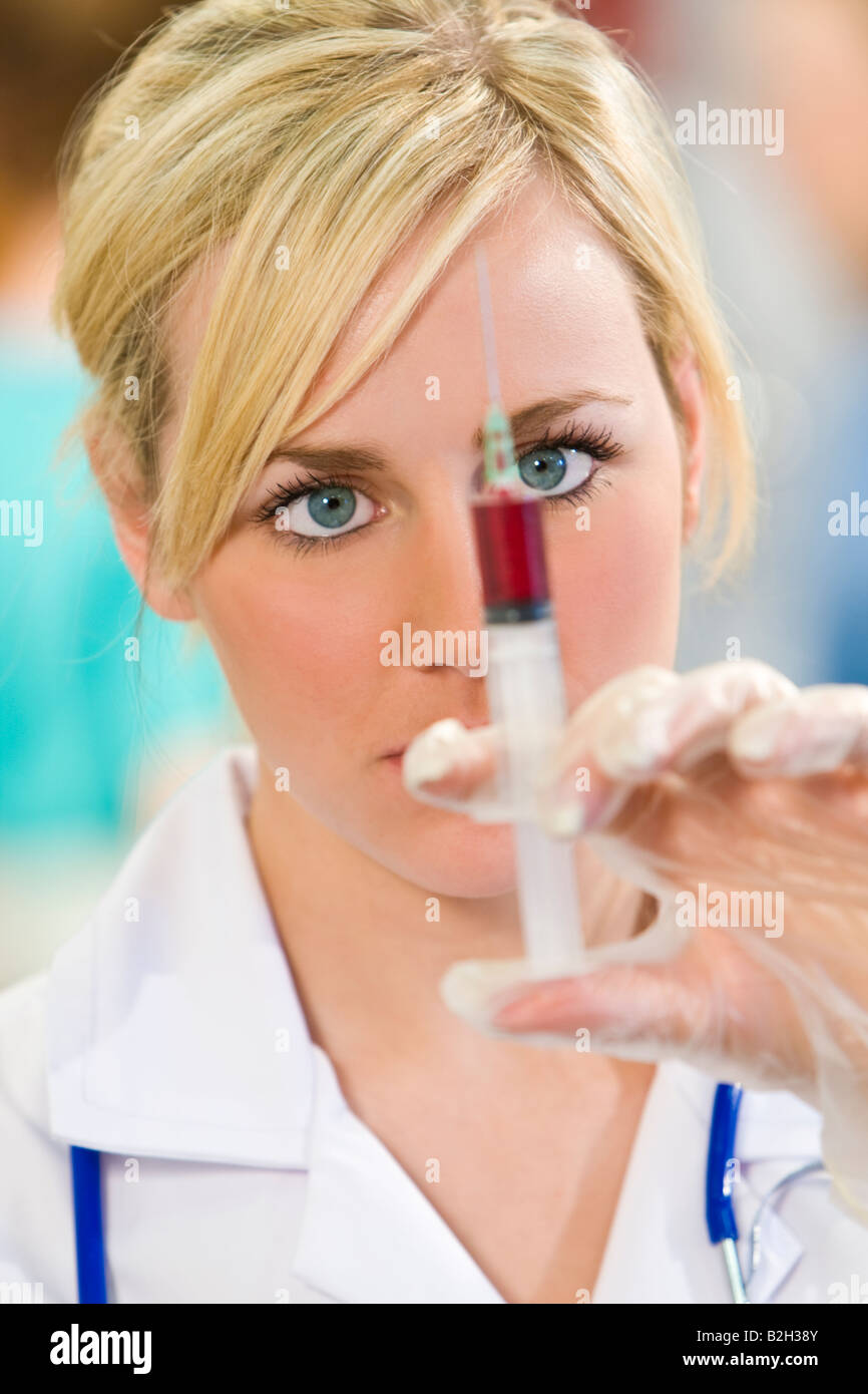 A pretty young female nurse with a stethoscope examines a prepares a syringe - Stock Image