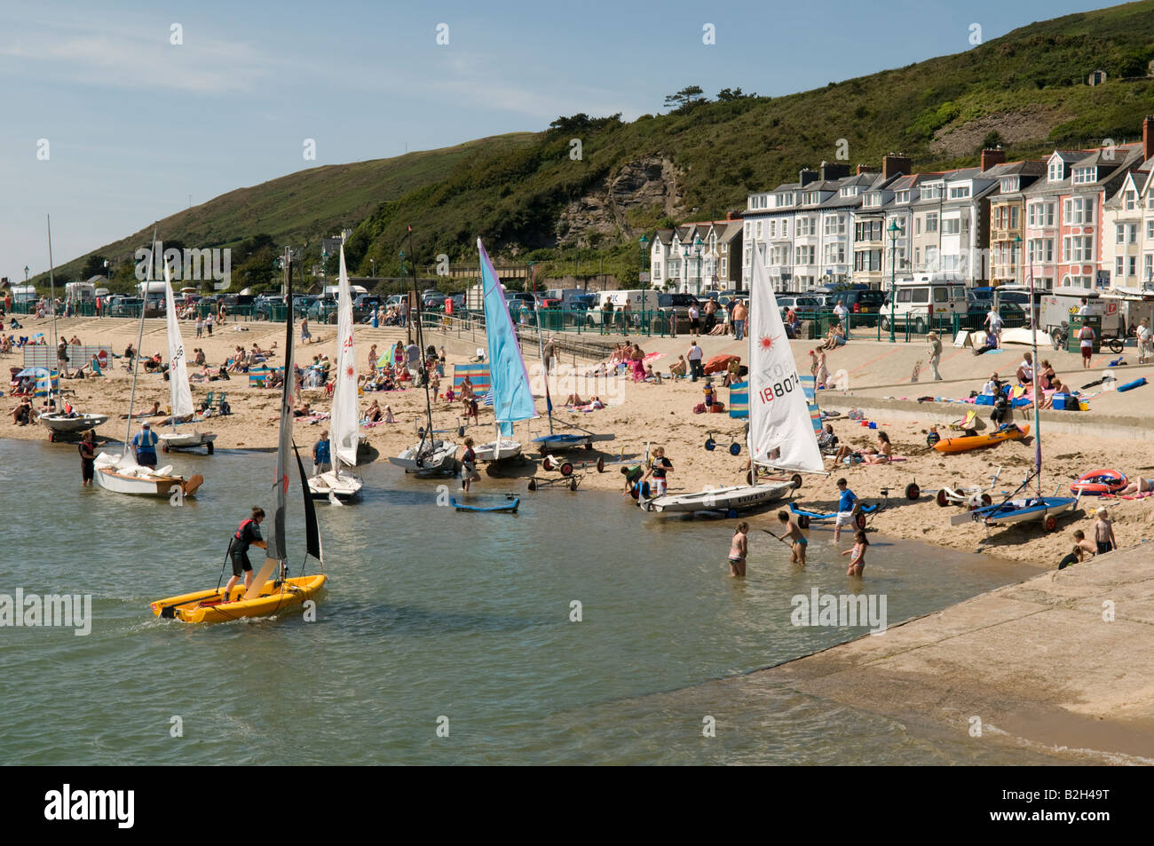 people and sailing dinghies on the sandy beach Aberdyfi seaside resort Snowdonia Wales summer afternoon - Stock Image