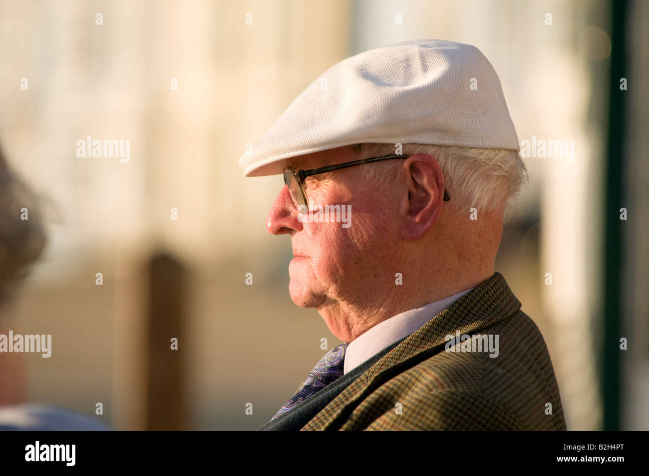 Old man wearing flat white cap and spectacles summer evening in profile UK 3881175336a
