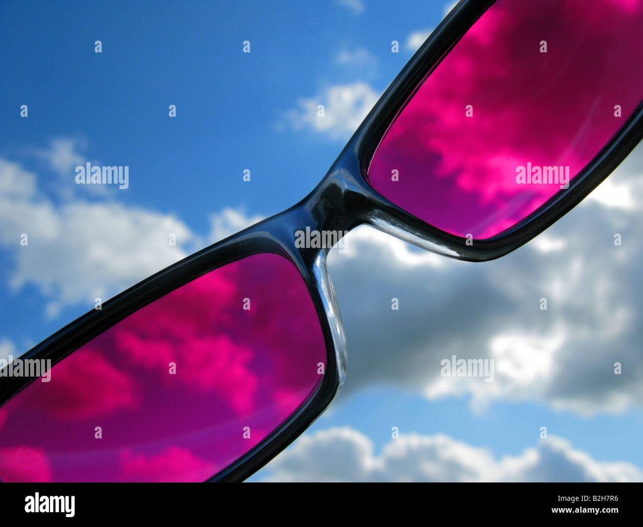 pink tinted sun glasses against blue sky - Stock Image