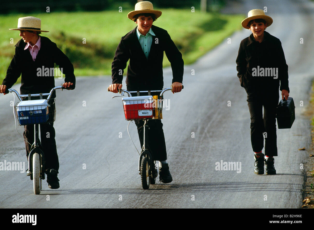 Amish children in traditional plain clothing on scooters on their way home from school, Lancaster County, Pennsylvania, - Stock Image