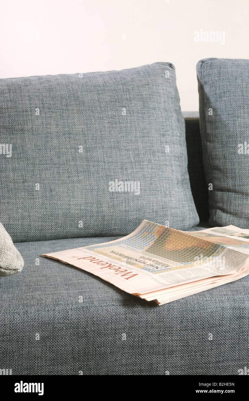 business paper lying on empty sofa - Stock Image
