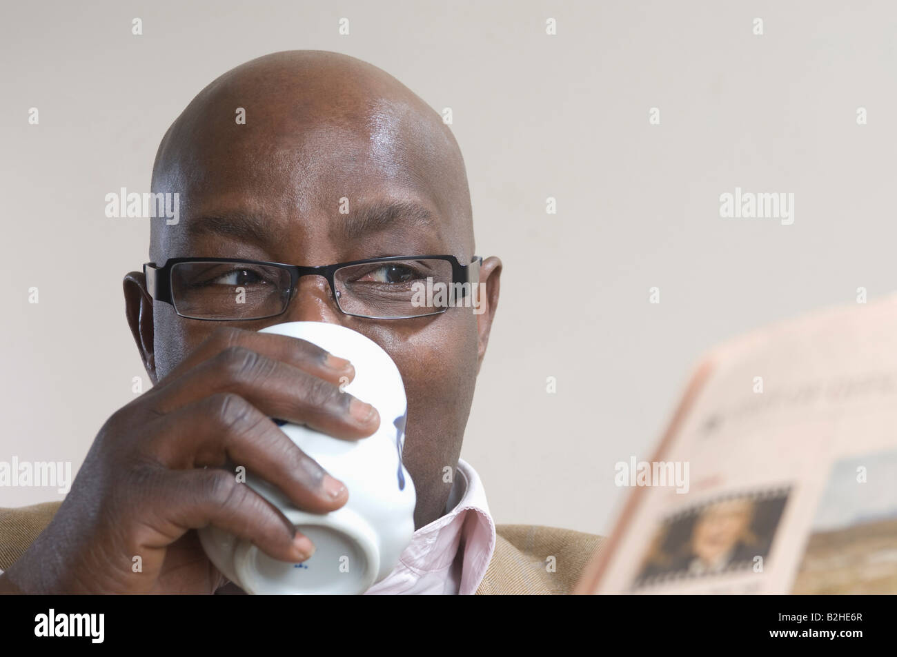 black businessman reading newspaper and drinking coffe - Stock Image