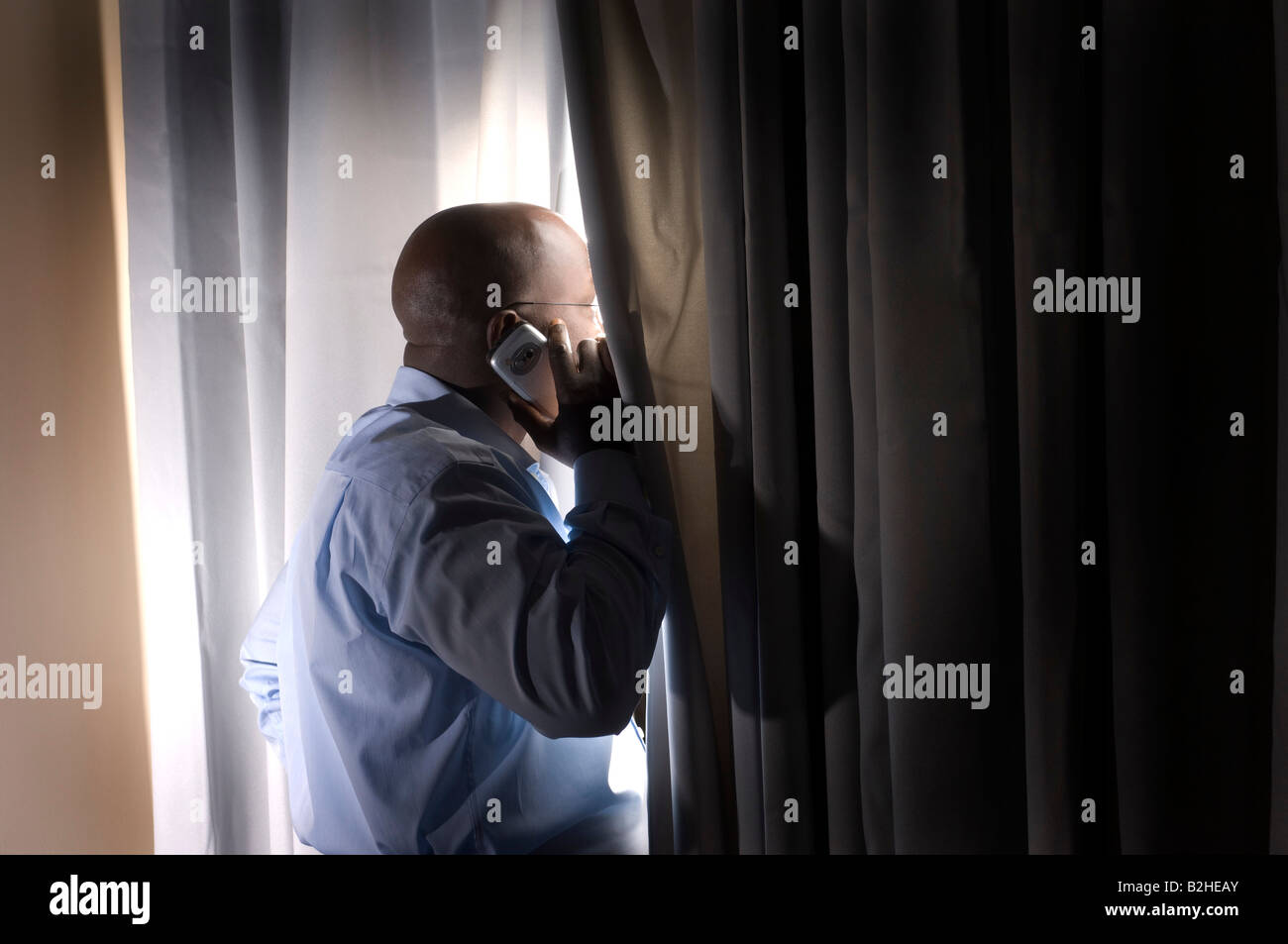 black businessman standing at window curtain talking on mobile phone - Stock Image