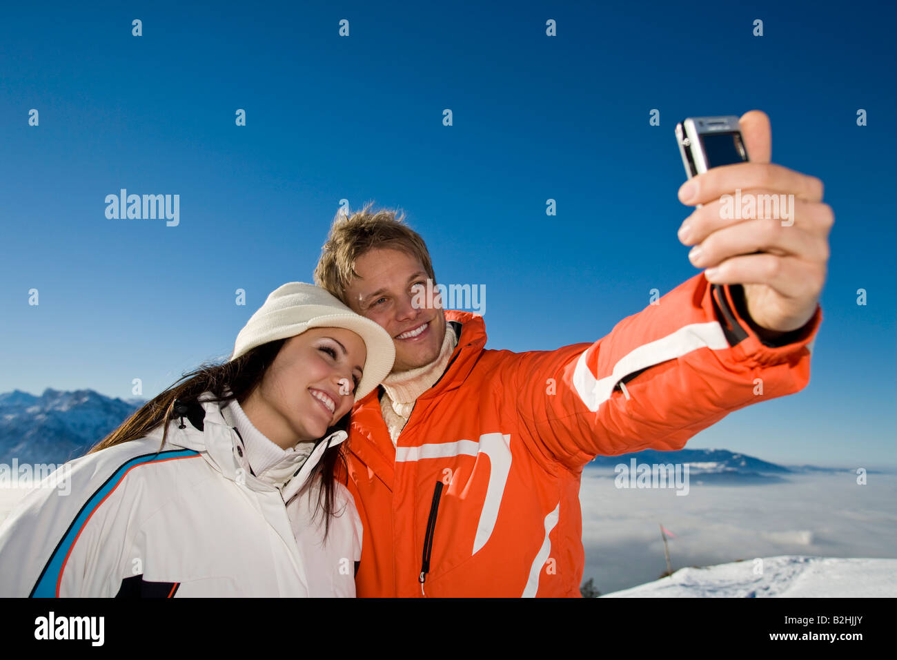 young couple in the mountains taking photo of themselves - Stock Image