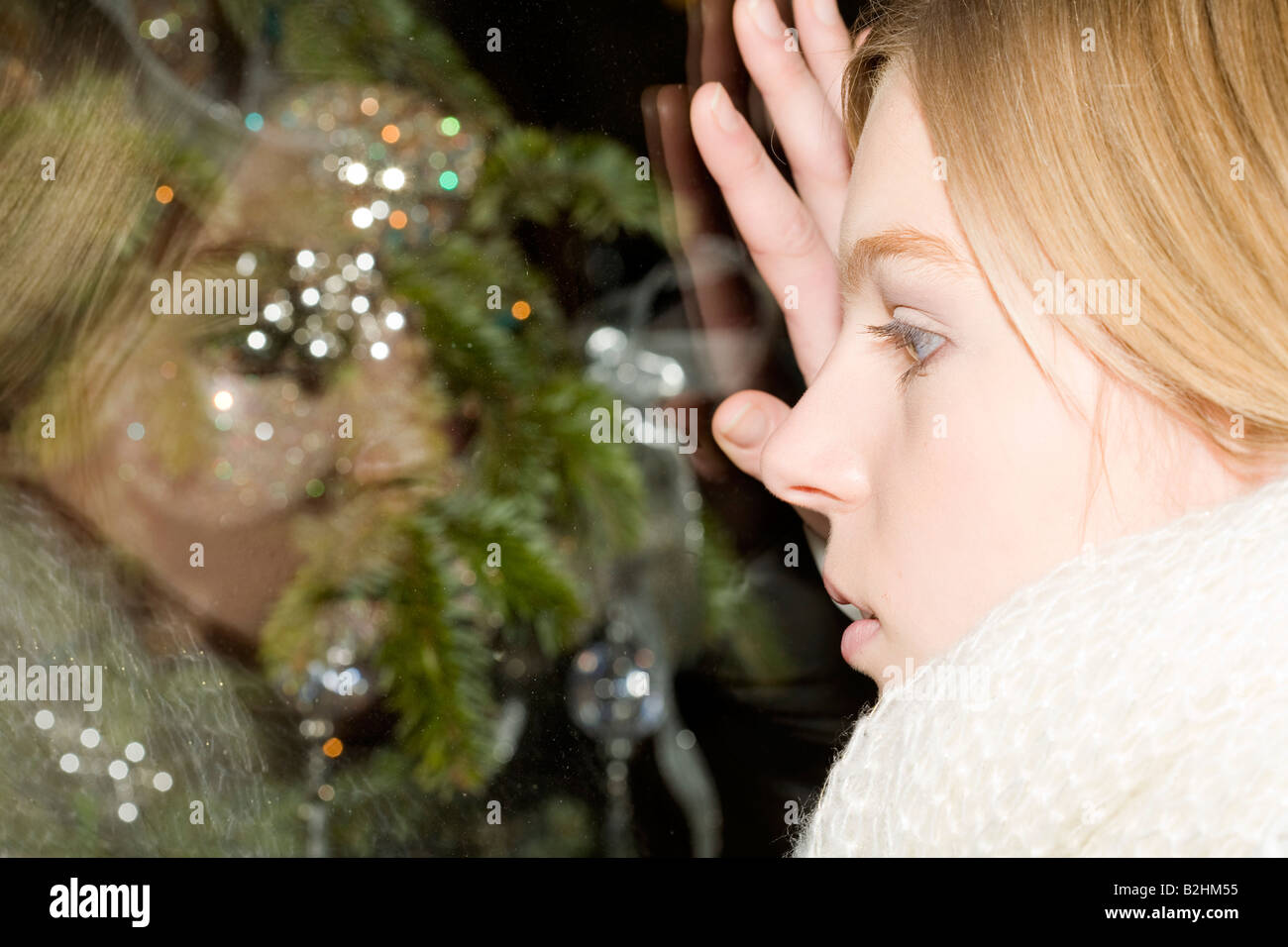 headshot of young woman looking through shop window with christmas decoration - Stock Image