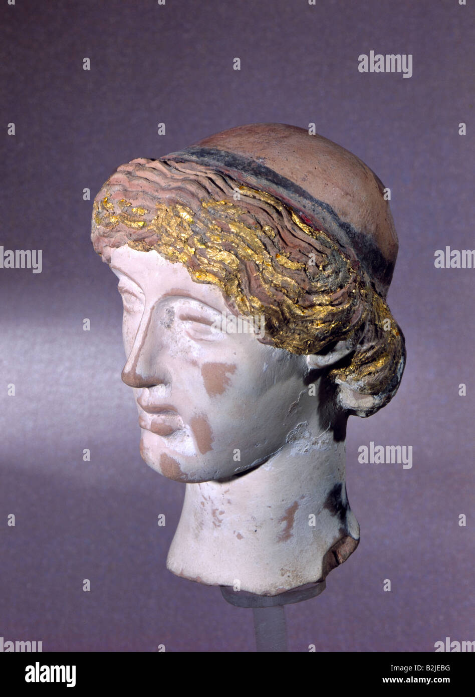 fine arts, ancient world, Italy, sculpture, head of a goddess, height 6.5 cm, terra cotta, painted, partly guilded, - Stock Image