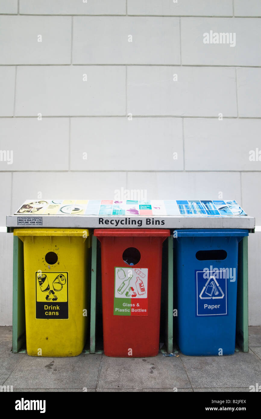 Three colour coded plastic recycling bins for aluminium drink cans, glass and plastic, and paper. - Stock Image
