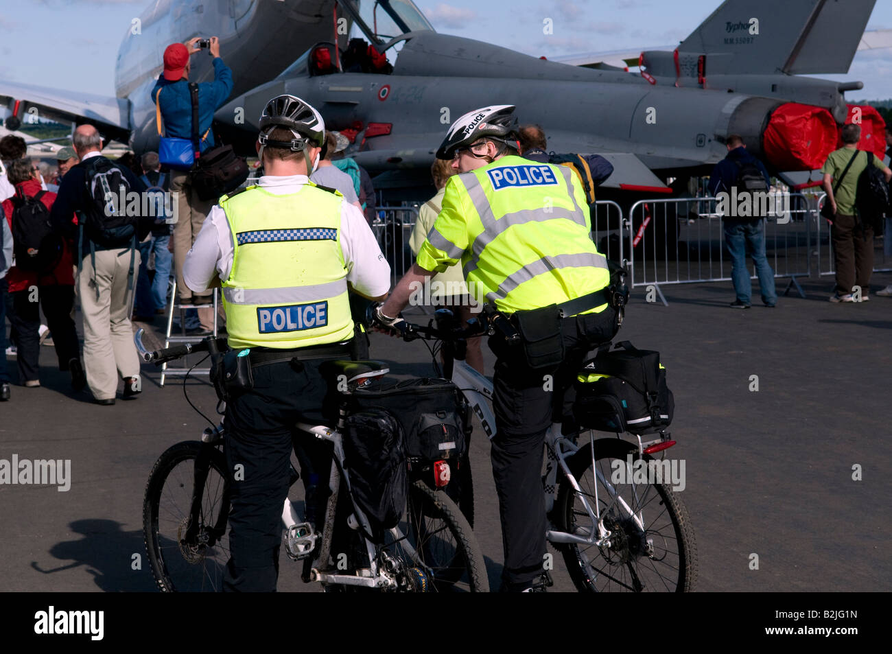 Two 2 police men on bycycles in yellow jackets sitting talking at a public event at the Farnborough air show close - Stock Image