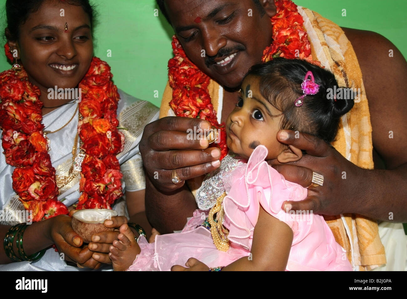 Parents carrying out Namakaran naming ceremony ritual father whispers name into the girls ear and she drinks honey - Stock Image
