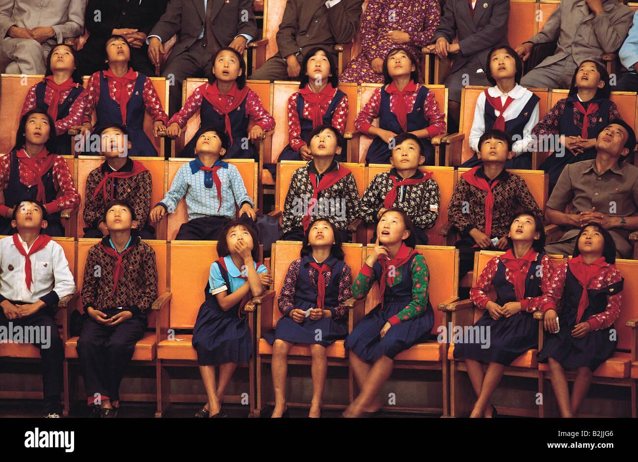 Korean school children audience . Looking up during acrobats show. - Stock Image