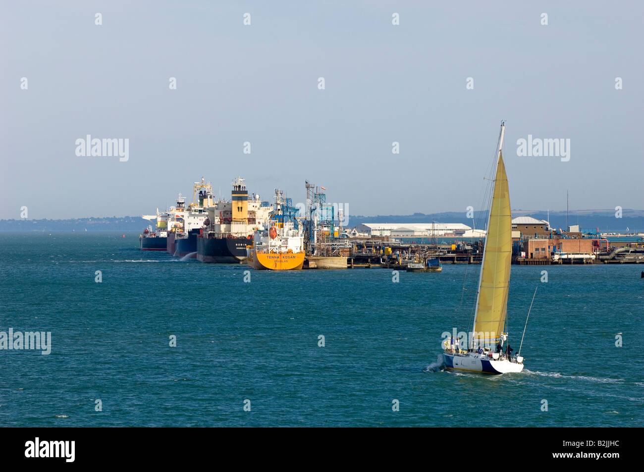 Yacht sailing by harbour terminal Southampton United Kingdom - Stock Image