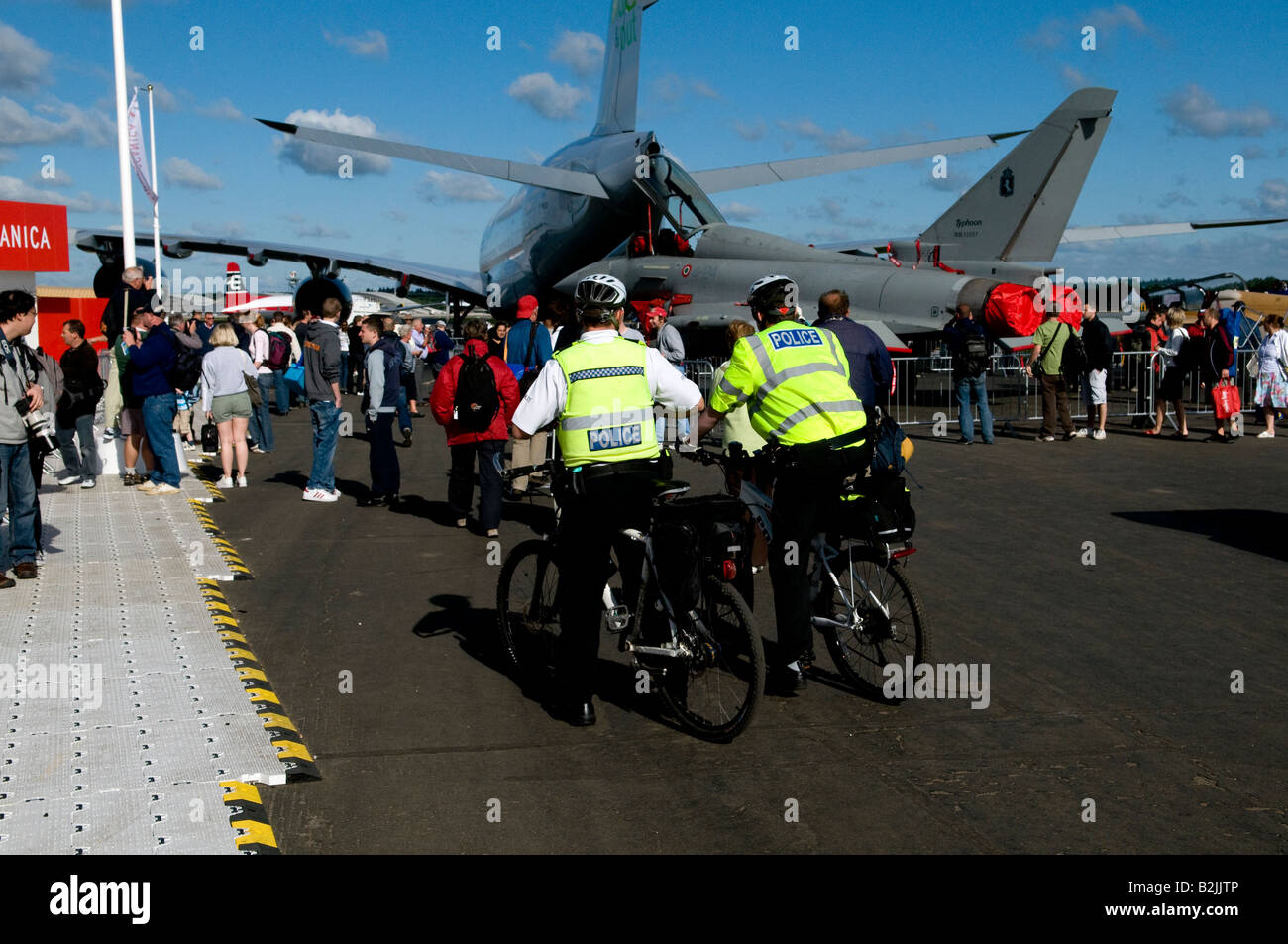 Two 2 police men on bycycles in yellow jackets sitting talking at a public event at the Farnborough air show wide - Stock Image