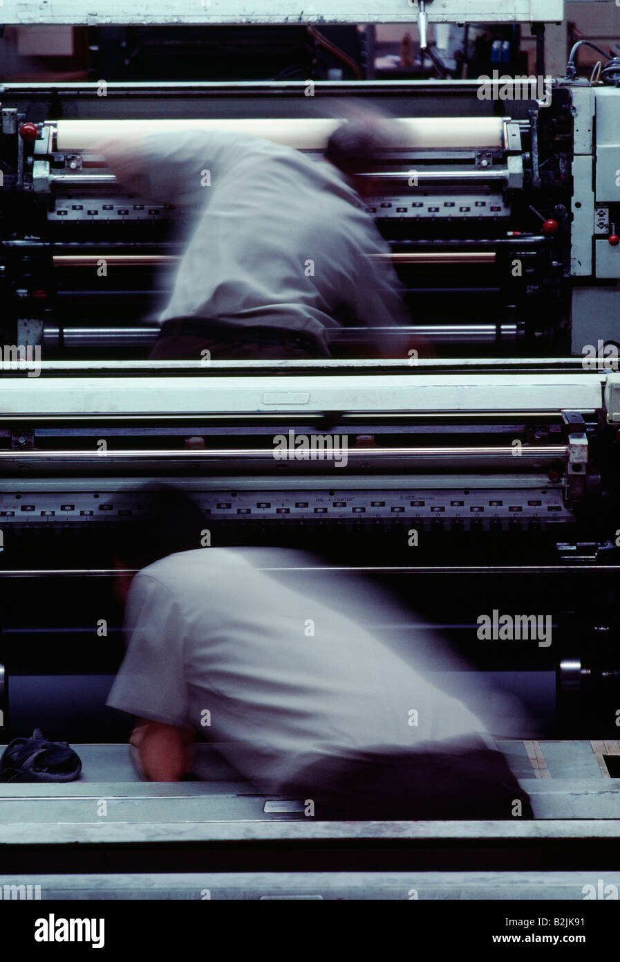 Two pressman in a blur of action while working on a commercial offset printing press - Stock Image