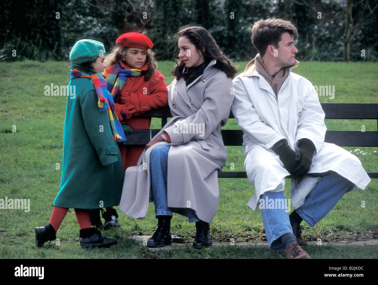 young couple having in argument in park in front of their children - Stock Image