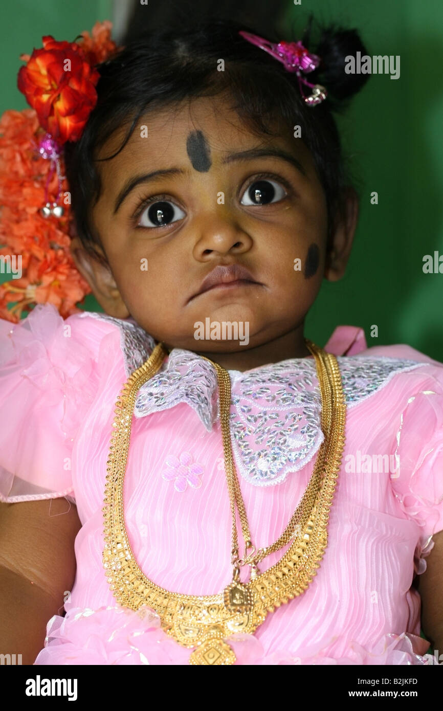 Portrait of a young Hindu girl with black spot make-up against the evil eye during her Namakaran naming ceremony - Stock Image