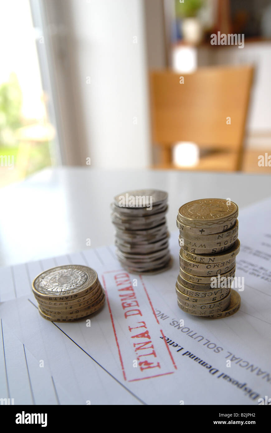 A stack of coins being counted, trying to pay the bills / final demand / reminder / red bill. - Stock Image