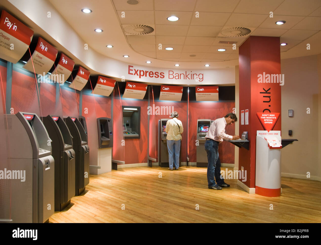 People using automated self service machines at a branch of HSBC bank - Stock Image