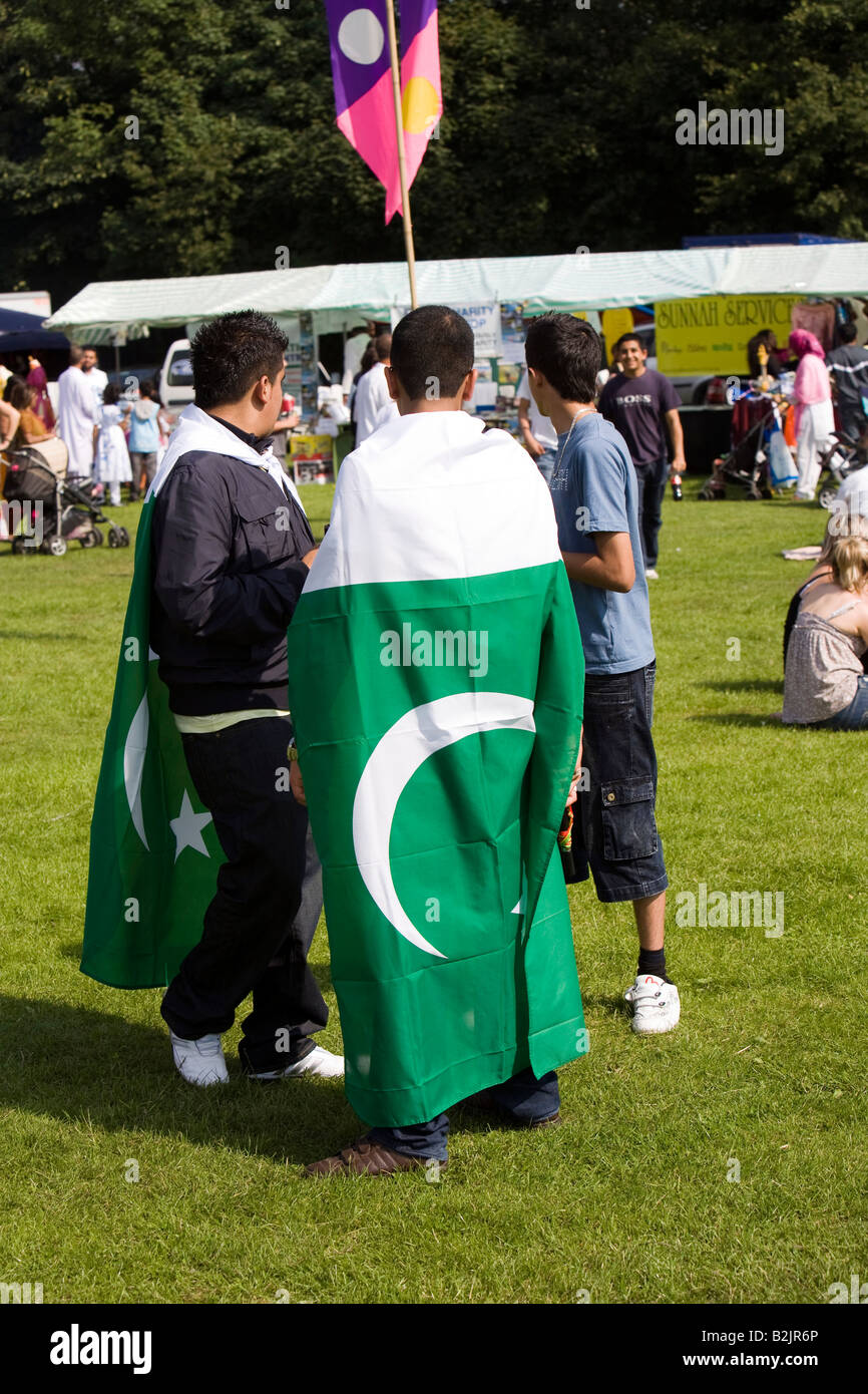 UK England Manchester Platt Fields Mega Mela young Pakistani men draped in national flag - Stock Image
